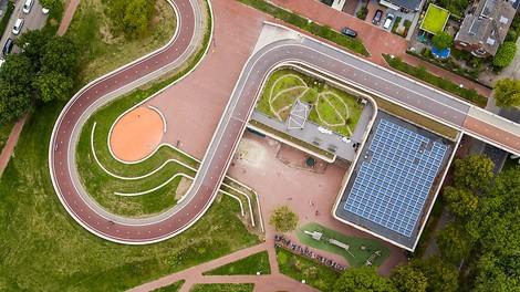 Eine Fahrradbrücke, die zwei Stadtteile miteinander verbindet und in die eine Schule eingebaut ist.